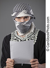 terrorist demands - terrorist in headscarf reading demands...
