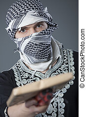 man with mail bomb - male terrorist in headscarf holding...