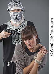 hostage - female hostage and hijacker with gun over grey...