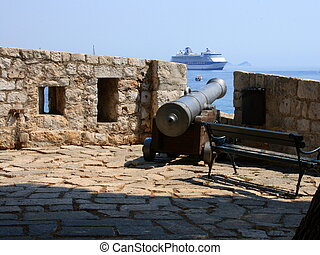 Cannon and cruise ship - Old cannon and cruise ship in...