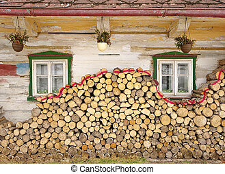 Stack of wood near old cottage windows