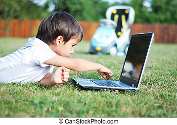 Cute kid is laying on laptop in beautiful environment