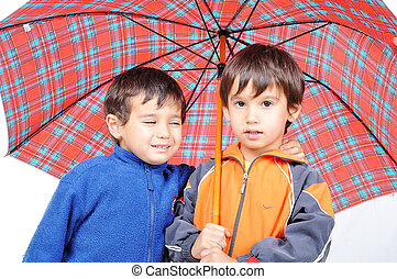 Very cute little boys in autumn clothes and with umbrella isolated