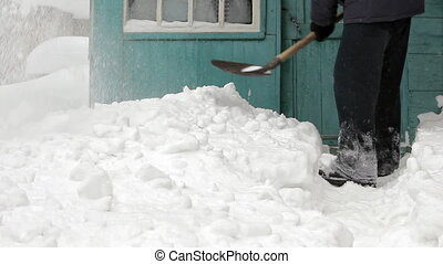 Man clearing snow off with shovel against house