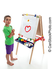Young child standing at art easel - A young boy child stands...