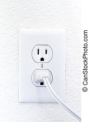 electric outlet on white wall with cord