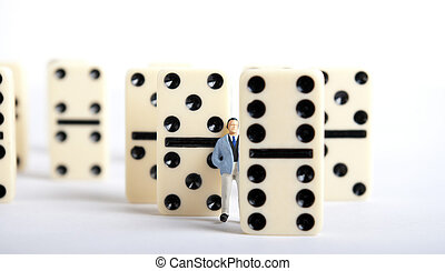 domino - one man standing on pile of domino cubes
