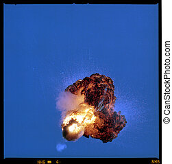 Explosion against blue sky - An object blowing apart in an...