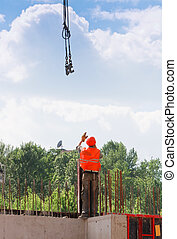 Rigger builder worker operating with straps - Rigger builder...