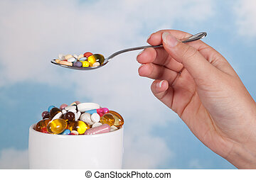 Having pills for breakfast - Hand holding a spoonful of...
