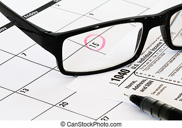tax due date with calendar, pen and reading glasses