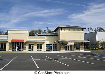 upscale beige strip mall with tin roof, stone accents, and...
