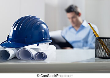 hardhat and blueprint on desk, with architect in background...