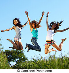 girlfriends jump in green grass field