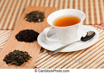Cup of tea and dried tea leaves - A cup of tea near three...