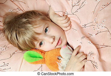 Kid in bed with toy