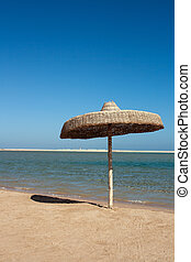 Cane umbrella on sandy beach of Red Sea, Egypt