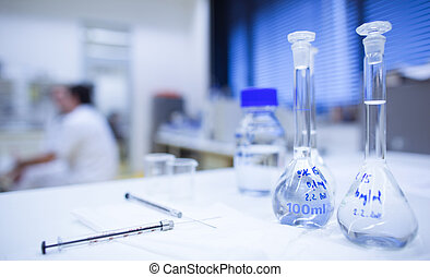 chemistry lab shallow DOF; focus on the glassware in the...