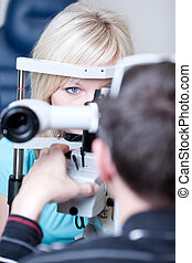 optometry concept - pretty young female patient having her...