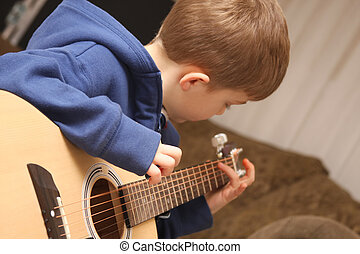 Strumming Guitar Boy - Young Boy strumming the guitar during...
