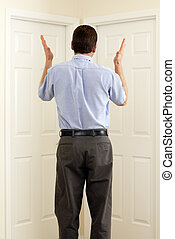 Indecision - Man between two doors with hands in the air not...