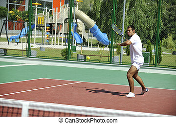 young man play tennis outdoor on orange tennis court at...