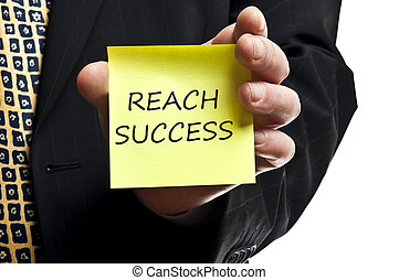 Reach succes post it in business man hand