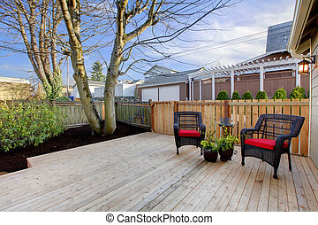 Deck with two chairs and fenced yard near home exterior shot...