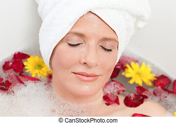 Relaxed woman taking a relaxing bath with a towel on her...