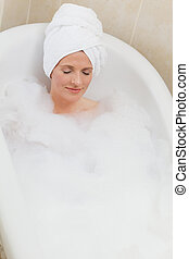 Lovely woman taking a bath with a towel on her head