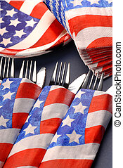 A 4th of July tablesetting with cups, plates, napkins and silverware
