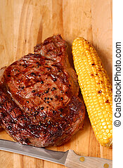 Grilled BBQ ribeye steak with corn