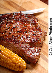 Grilled BBQ ribeye steak with corn and knife