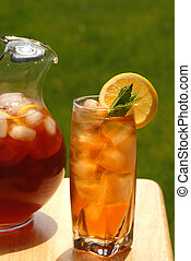 Glass of iced tea with pitcher of tea next to it - A glass...
