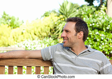 Portrait of a man sitting on a  bench
