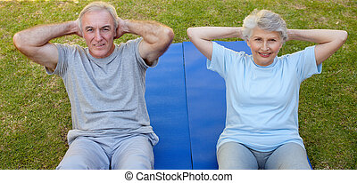 Retired couple doing their streches in the garden