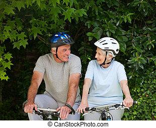 Senior couple mountain biking outside