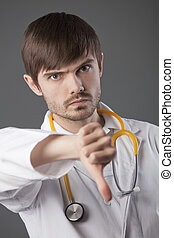 doctor with thumbs down sign - unhappy male doctor with...