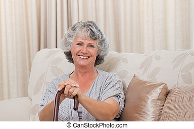 Woman with her walking stick at home