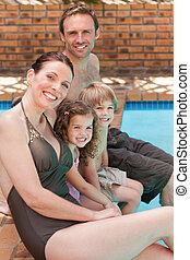 Happy family beside the swimming po
