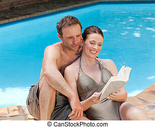 Couple reading a book beside the swimming pool