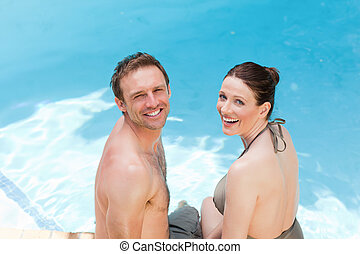 Couple looking at the camera beside the swimming pool