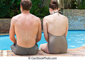 Couple sitting beside the swimming pool