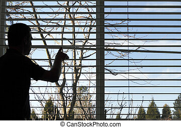 Bored Inside - Silhouette of a man looking out a window,...