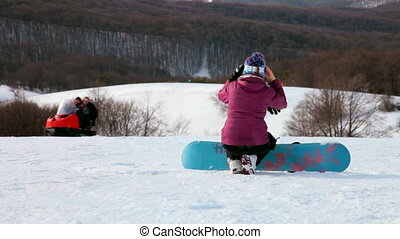Snowboarder on mountain - Snowboarder taking a break during...