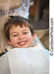 at the dentist - young boy in a dentist chair smiling