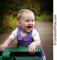 Laugh of happy little baby girl playing outdoors