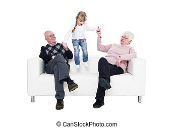 Little Girl with her grandparents in a sofa isolated on...