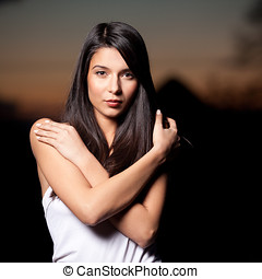 a portrait of a young, beautiful woman, shot outside, on a sunset background. she has a white top on and she is holding her shoulders with her hands.