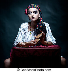 a portrait of a gypsy fortune teller mixing the tarot cards...